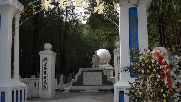 Une partie du mémorial de Norman Bethune. C'est ici que le médecin canadien a été enterré après sa mort le 12 novembre 2019, avant que ces restes ne soient transférés dans un autre cimetière des Martyrs,  à Shijiazhuang, le chef-lieu du Hebei. Novembre 2019.   On voit une statue, un globe-terrestre, un portail et des couronnes de fleurs.