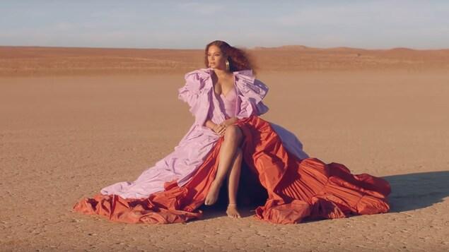 Beyoncé assise dans le désert portant une robe rose et rouge