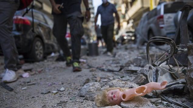 Une poupée au sol dans les débris.