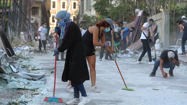 Des hommes et des femmes déblaient les rues à l'aide de balais ou de pelles.