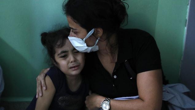 Une femme serre une enfant qui pleure dans ses bras.