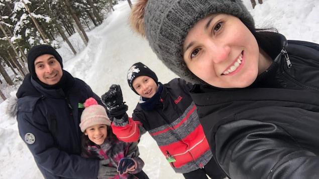 Une selfie d'une famille de 4, en hiver, dans une forêt