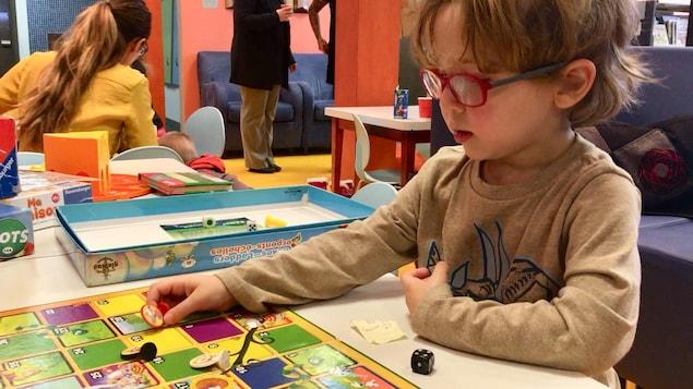 Un enfant portant des lunettes est installé à une table et joue à un jeu.