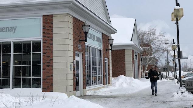 Un homme marche devant une bibliothèque.