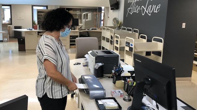 Une dame imprime un passeport vaccinal.