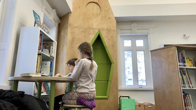 Deux enfants attablés devant des livres à la bibliothèque.