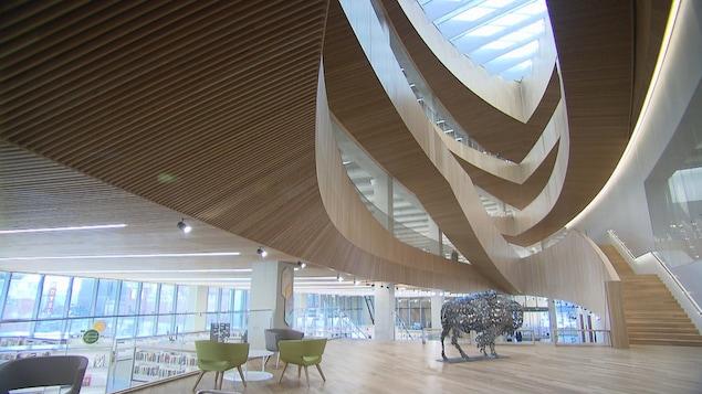 Une vue des étages de la bibliothèque centrale de Calgary avec les escaliers en bois. Il y a une sculpture d'un taureau en métal, qui représente la Ville de Calgary.