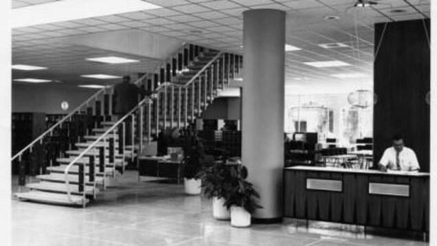 Une vieille photo de l'entrée de la bibliothèque, avec un escalier et une réception.