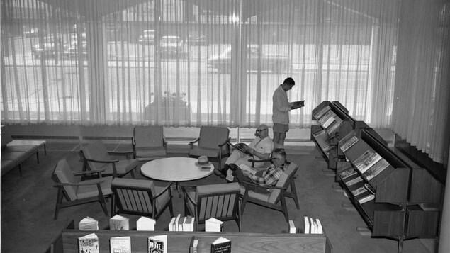 Trois personnes ont le nez dans des livres, autour d'une table avec des chaises.