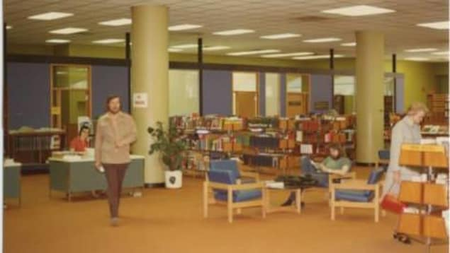 Quatre visiteurs sont dans une bibliothèque remplie de livres et de chaises.