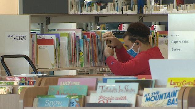 Une personne portant un masque cherche un livre rangés dans une étagère d'une bibliothèque