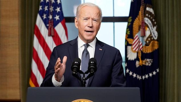 Joe Biden parle dans un micro, derrière un lutrin arborant le logo du président des États-Unis et devant le drapeau américain.