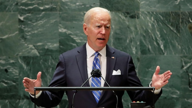 Biden parle devant un lutrin, les bras ouverts.