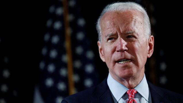 Joe Biden regarde vers la droite, devant des drapeaux américains