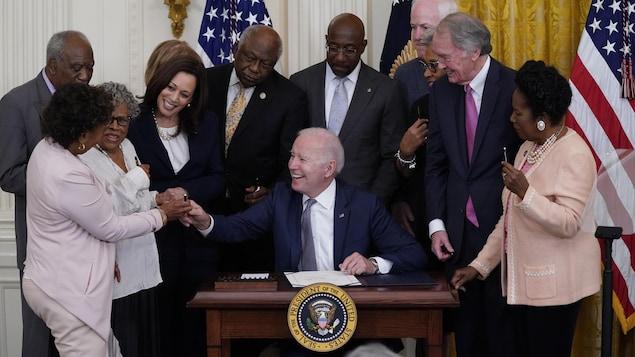 Au milieu d'un groupe d'élus réunis à la Maison-Blanche, une représentante tend un stylo à Joe Biden, qui sourit, tout comme Kamala Harris.