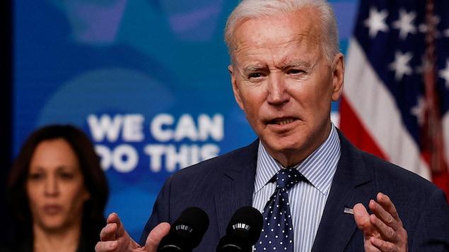 Joe Biden, in front of a microphone, speaks to reporters with Kamala Harris behind him.