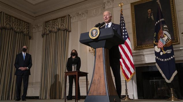 Joe Biden parle aux reporters devant un drapeau américain et un portrait d'Abraham Lincoln, sous le regard de John Kerry et de Kamala Harris.