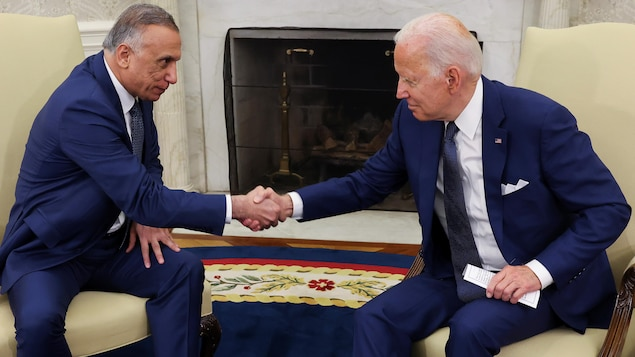 Tous deux assis, le président Joe Biden et le premier ministre irakien al-Kadhimi, réunis à la Maison-Blanche, se serrent la main.