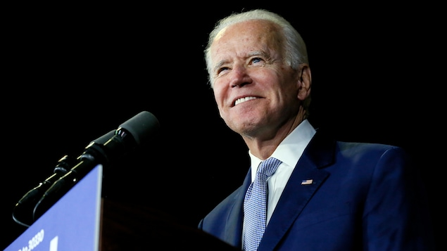 Joe Biden, souriant, devant un micro