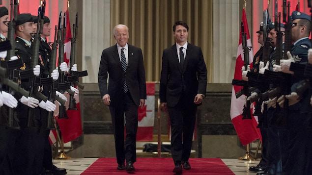 Les deux hommes politiques marchent sur un tapis rouge entre deux rangées de militaires canadiens.