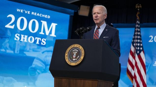 Joe Biden, regardant la caméra, à côté d'un drapeau américain, devant un large panneau disant : « Nous avons atteint 200 millions de doses. »