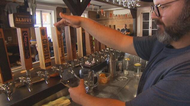 Mario Dugré rempli un verre de bière