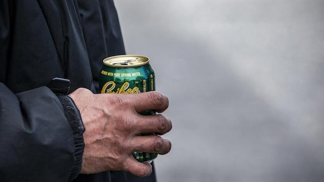 La main d'un homme tient une cannette de bière.