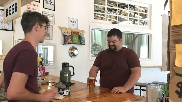 Adam Smith, copropriétaire de la microbrasserie Malty National à Regina, sert une bière à Matt Leisle, un fidèle client.