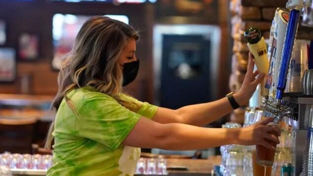 A waitress serves a beer in a bar.