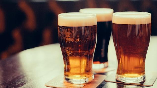 Des verres de bière sur une table de bois.