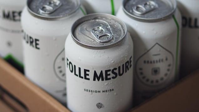 Des bières en canettes dans une boîte en carton.