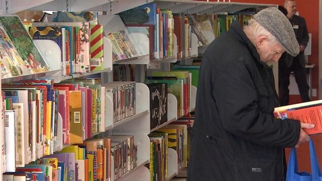Un homme lit un livre dans une bibliothèque.