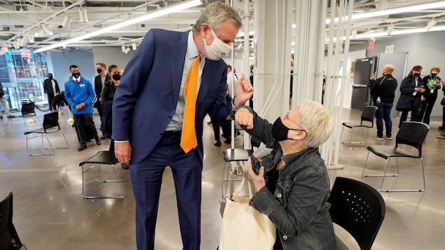 Le maire salue du coude une femme assise dans le centre de vaccination.