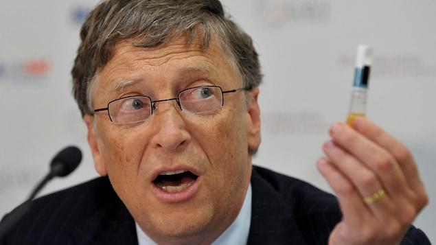 Bill Gates tient un flacon de vaccin lors d'une conférence de presse.