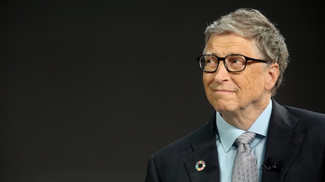 Bill Gates portant un veston, pris en photo sur un fond sombre.