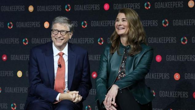 Un homme portant des lunettes est assis à côté d'une femme. Ils sourient.