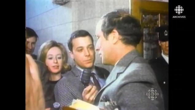 Pierre Elliott Trudeau devant des journalistes qui lui tendent le micro.