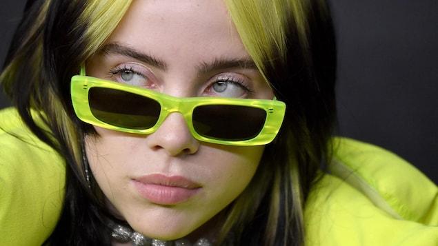 Une jeune femme portant des lunettes de soleil vertes.