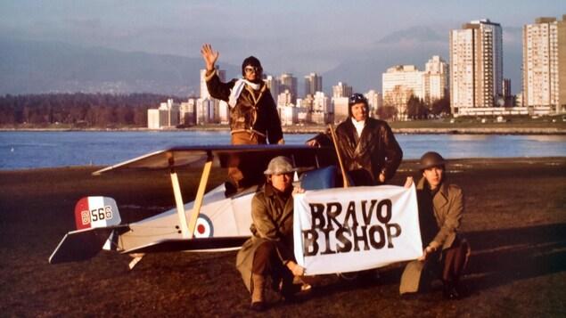 Quatre hommes en costume militaire devant et dans un biplan