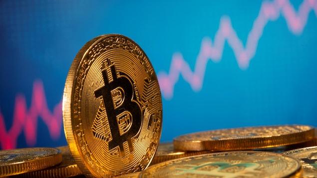 Une pièce illustrant un bitcoin devant un graphique boursier.