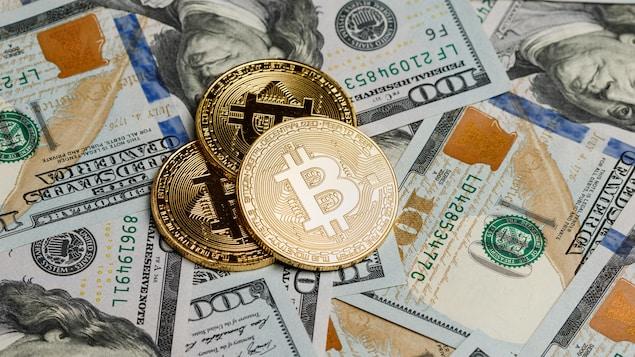 Des bitcoins sont déposés sur des billets de 100 $ américains.