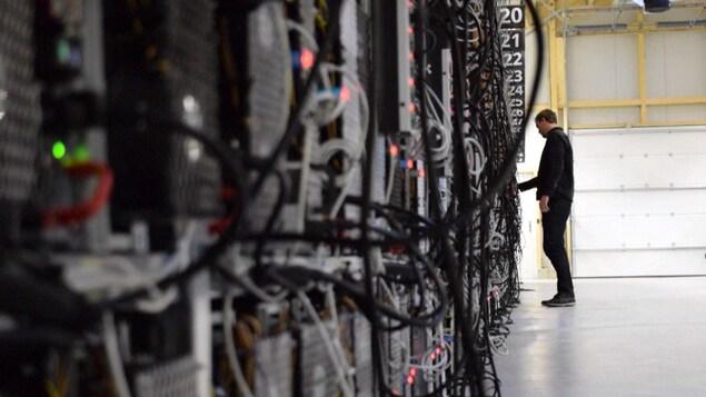 Un homme vérifie les fils d'un serveur d'une ferme de bitcoins.