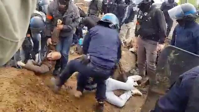 Des policiers utilisent la force pour arrêter des manifestants.
