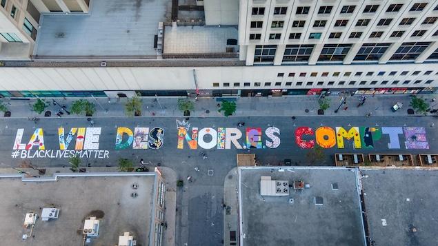 Vue des airs, une fresque, peinte sur le sol de la rue Sainte-Catherine à Montréal, une fresque indiquant « La vie de noir.e.s compte », avec la mention #BlackLivesMatter.