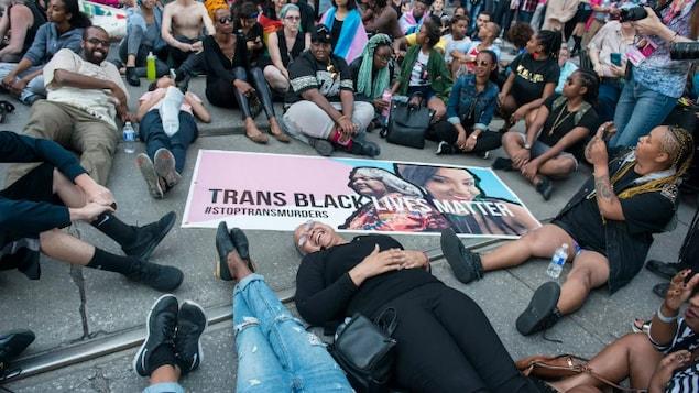 Des militants sont allongés sur le sol autour d'une grosse pancarte sur laquelle on peut lire : les vies des Noirs trans comptent