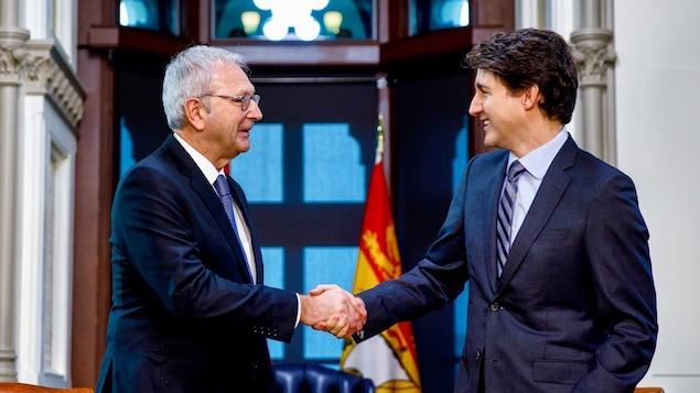 Blaine Higgs et Justin Trudeau se serrent la main.