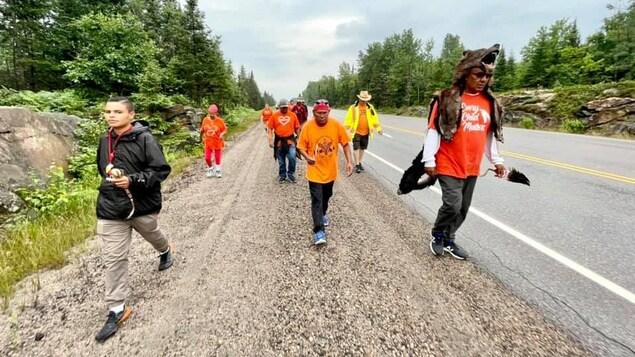 Le chef Vern Janvier marche avec d'autres personnes sur le bord de l'autoroute.