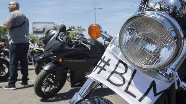 Plusieurs motos sont stationnées. Sur l'une d'elle, un morceau de tissu a été fixé sur lequel on peut lire BLM, les initiales de Black Lives Matter.