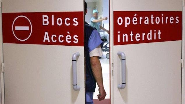 Porte entrouverte du bloc opératoire. On y voit un homme de dos face à un médecin.