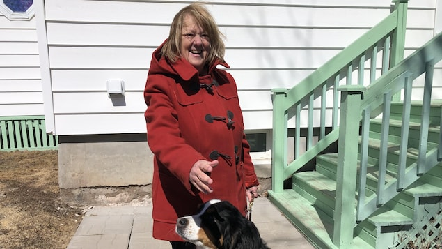 Une femme sourit à la caméra et pose avec son chien.